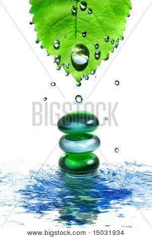 balancing spa shiny stones in water with leaf and drops isolated on white
