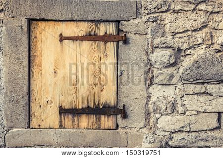 Wooden trap door with rusty hinges - Rustic architecture background with a stone wall of a german house with it's wooden trap door and the rusty hinges