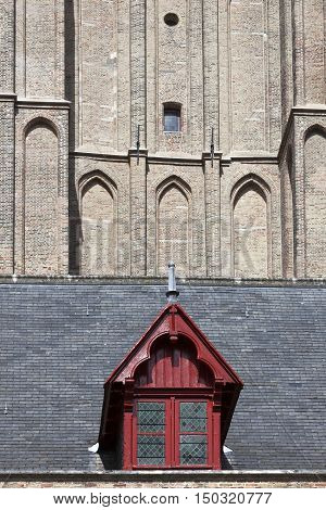 red wooden dormer window on cathedral onze lieve vrouw in the belgian city of brugge
