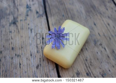 Natural soap with flower chicory on background of burlap