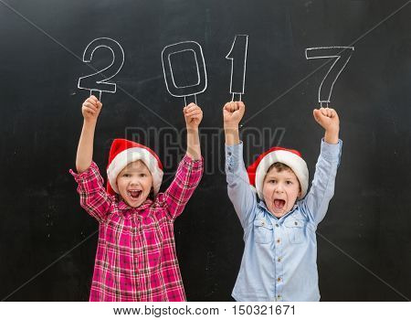 two little laughing children in red santa hats and hands up with note 2017 above their heads