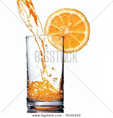 orange juice pouring into goblet with orange slice