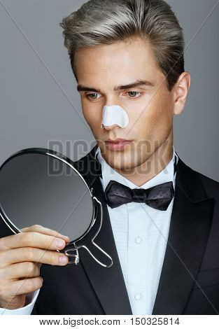 Man with cleaning strips for nose on his face. Well-groomed man in a tuxedo looking in the mirror. Grooming himself