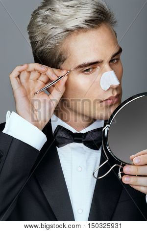 Gentleman concentrating on tweezing his eyebrows. Photo of classy gentleman looking in the mirror cares for his appearance. Grooming himself