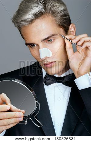 Young man tweezing the hair on his face. Photo of gentleman looking in the mirror cares for his appearance. Grooming himself
