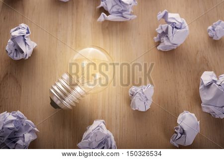 glowing lightbulb with crumpled paper ball on wooden table. concept for inspiration or idea under light bulb