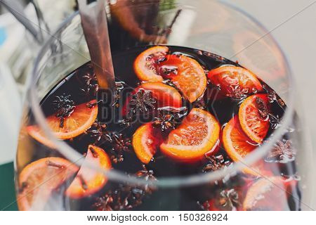 Making hot alcohol, mulled wine for sale at country fair. Glintwine from red wine with citrus and cloves in big glass, mixed with soup ladle. Closeup