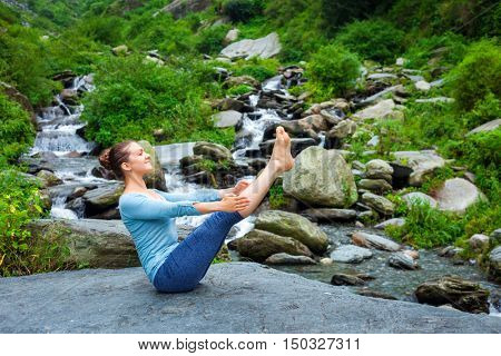 Yoga outdoors - young sporty fit woman doing Ashtanga Vinyasa Yoga asana Navasana - boat pose  - in Himalayas at tropical waterfall. Himachal Pradesh, India