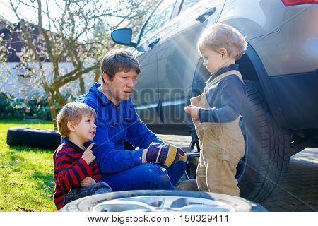Two little kid boys and  father changing wheels on car with pneumatic wrench. Man in uniform teaching his sons working with tools.