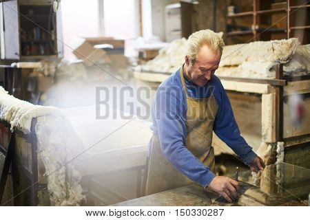 The master cuts the glass with a glass cutter