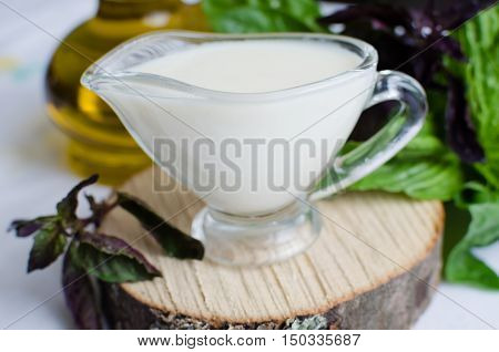 Classic European white sauce Bechamel in saucer with basil and olive oil on white background. Bechamel sauce for traditional European dishes. Italian food concept. Selective focus.