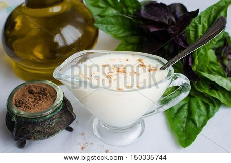 Classic European white sauce Bechamel in saucer with nutmeg, basil and olive oil on white background. Bechamel sauce for traditional European dishes. Italian food concept. Selective focus.