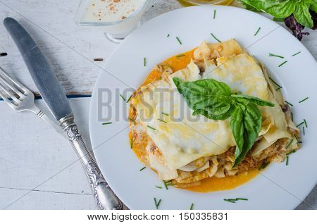 Traditional lasagna made with minced beef bolognese sauce and bechamel sauce topped with basil leaves. Portion of tasty homemade lasagna on white wooden table. Italian food concept. Top view.
