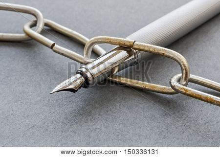 Closeup of a silver fountain pen and a chain