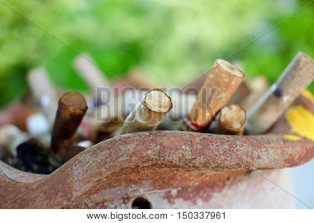 Cigarette butts in the clay pot with green background