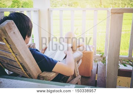 Young man reading a book lying in relaxing bed at terrace with green nature view