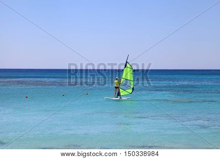 Back view of young woman windsurfer in Crete island, Greece