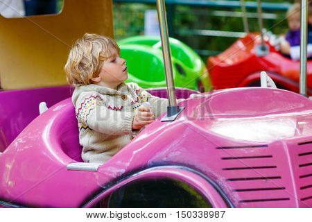Funny little kid boy riding on car on roundabout carousel in amusement park. Happy toddler having fun outdoors on sunny day.