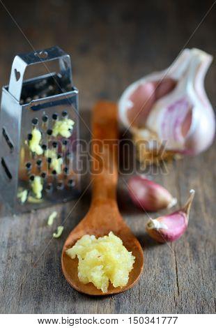 Garlic in spoon on wooden background