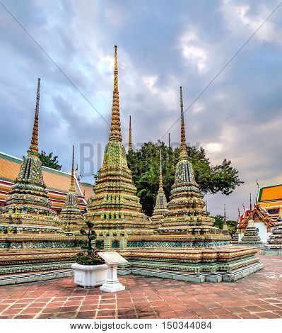 Classical Thai architecture in Wat Pho public temple at stormy sunset cloudy sky Bangkok Thailand. Wat Pho known also as the Temple of the Reclining Buddha.