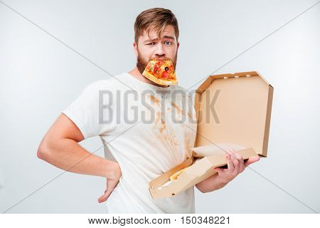 Funny bearded man with pizza slice in his mouth looking at camera isolated on white background