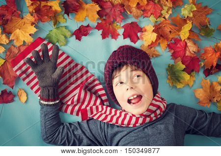 seven years old boy dreaming in autumn. Child in hat and scarf and maple leaves on blue background
