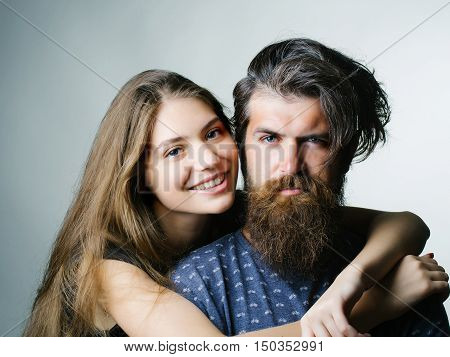 Young couple of pretty smiling girl hugging man hipster with bearded handsome serious frown face in blue clothes on gray background studio