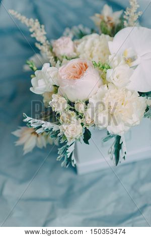 floral arrangement of delicate roses lilies carnations in a white box