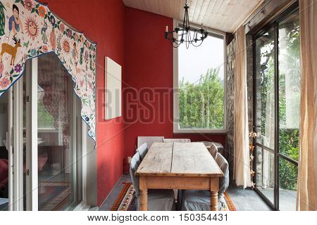 Interior, veranda with old dining table, picture on the wall