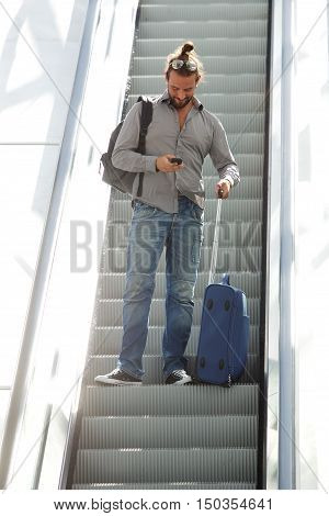 Traveling Man Standing On Escalator Looking At Mobile Phone