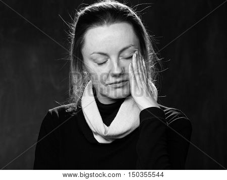 Close up sad woman wiping the tears away black and white