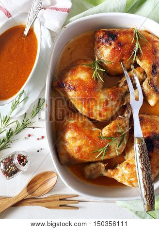 Roast chicken with sauce and rosemary in ceramic pot