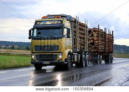 SALO, FINLAND - SEPTEMBER 4, 2015: Yellow Volvo FH16 logging truck transports spruce logs along road on a rainy day with headlights reflecting on wet asphalt.