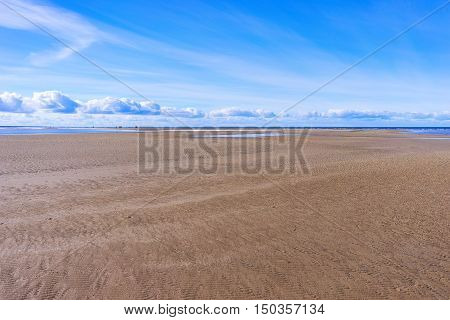 People walk in a day on a wide yellow sandy beach at low tide in the Baltic Sea in spring