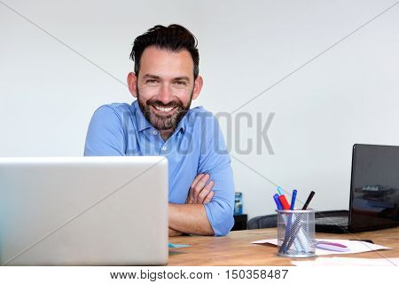 Happy Mature Business Man Sitting At His Office Desk