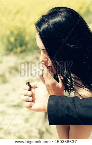 Man hand offers to woman beautiful brunette gas lighter to light cigarette for smoking on nature