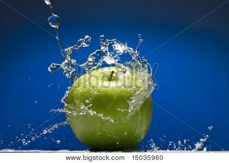 Maçã verde com respingos de água no fundo azul