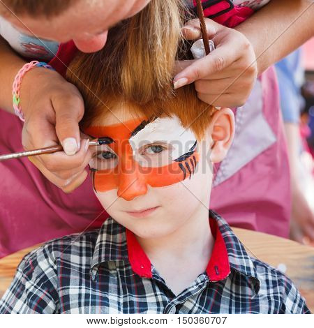 Child animator, artist's hand draws face painting to little boy. Child with funny face art. Painter makes tiger eyes on boy's face. Children holiday, event, birthday party, entertainment.