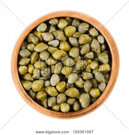 Capers in wooden bowl on white background. Edible flower buds of Capparis spinosa, caper bush or Flinders rose. Pickled caper buds are used as seasoning or garnish. Isolated macro food photo close up.