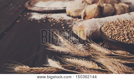 Bread sorts border on wood with copy space background. Brown and white whole grain loaves still life composition with wheat ears scattered around. Bakery and grocery food store concept.