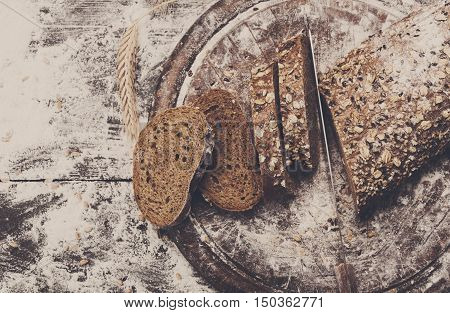Bakery and grocery concept background. Fresh, healthy whole grain sliced rye bread loaf, sprinkled flour, wheat ears on rustic table and wooden round desk, food closeup.