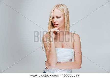 Portrait of a pensive thougtful pretty blonde girl thinking about something isolated on the gray background