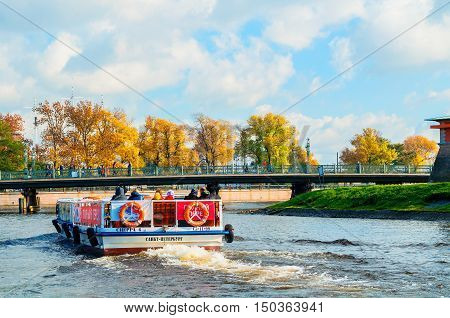 ST PETERSBURG RUSSIA-OCTOBER 3 2016. Ioannovsky or St John bridge and sailboat floating on the Kronverk strait in St Petersburg Russia. Architecture landmark of St Petersburg in autumn sunny day