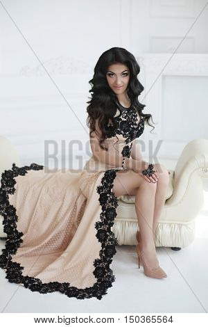 Beauty Fashion Glam Brunette Model  In Elegant Dress With Long Wavy Hair Style. Beautiful Woman Sitt