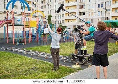 MOSCOW, RUSSIA - JUN 27, 2016: Cameraman and assistants prepare shooting reportage from children playground in courtyard of residential houses.