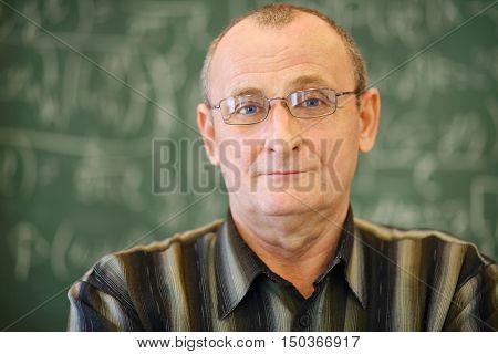 Old teacher in glasses near blackboard in school classroom, shallow dof