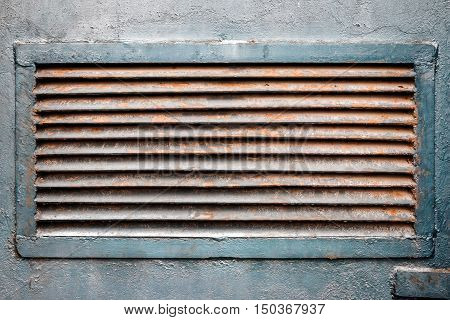 Rusty old ventilation grille on metal wall painted in blue