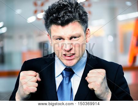 Businessman Clenching Fists To Motivate Team In Office