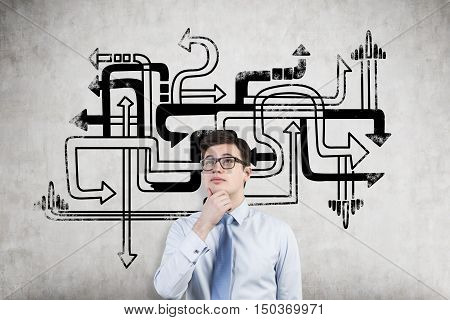 Young businessman choosing his way in life standing near arrow pipeline sketch on concrete wall. Concept of tough decision