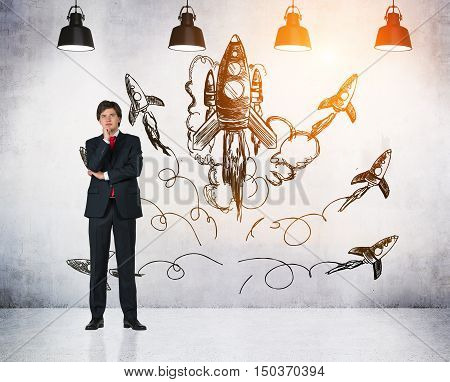 Businessman in suit posing near concrete wall with black rocket images on it. Concept of new project launch. Toned image